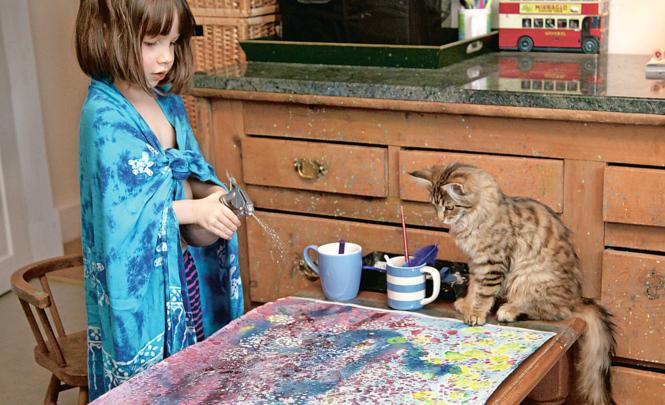 Katze Thula schaut gebannt zu, wenn Iris Grace Farbe auf ihre Bilder sprüht.