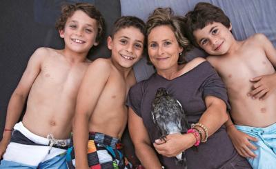 Sam Bloom mit ihren drei Buben: Die zutrauliche Elster Penguin hat es sich auf ihrer Brust bequem gemacht.