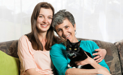 Kuschelzeit im Wohnzimmer: Mama Karin (mit Katze Nala) und Tochter Jana sitzen vertraut zusammen.